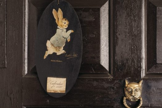 An oval board hanging on a door in the Entrance Hall of Hill Top, with a picture of Peter Rabbit ©Nationaltrustimages-Geoffrey-Frosh