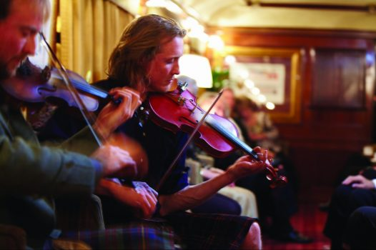 Belmond Royal Scotsman - Evening Entertainment Violins playing in the Bar Car ©Matt Hind