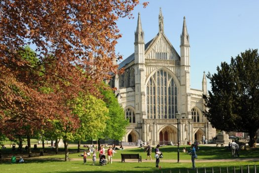 Winchester Cathedral and people view on a summers day through the trees